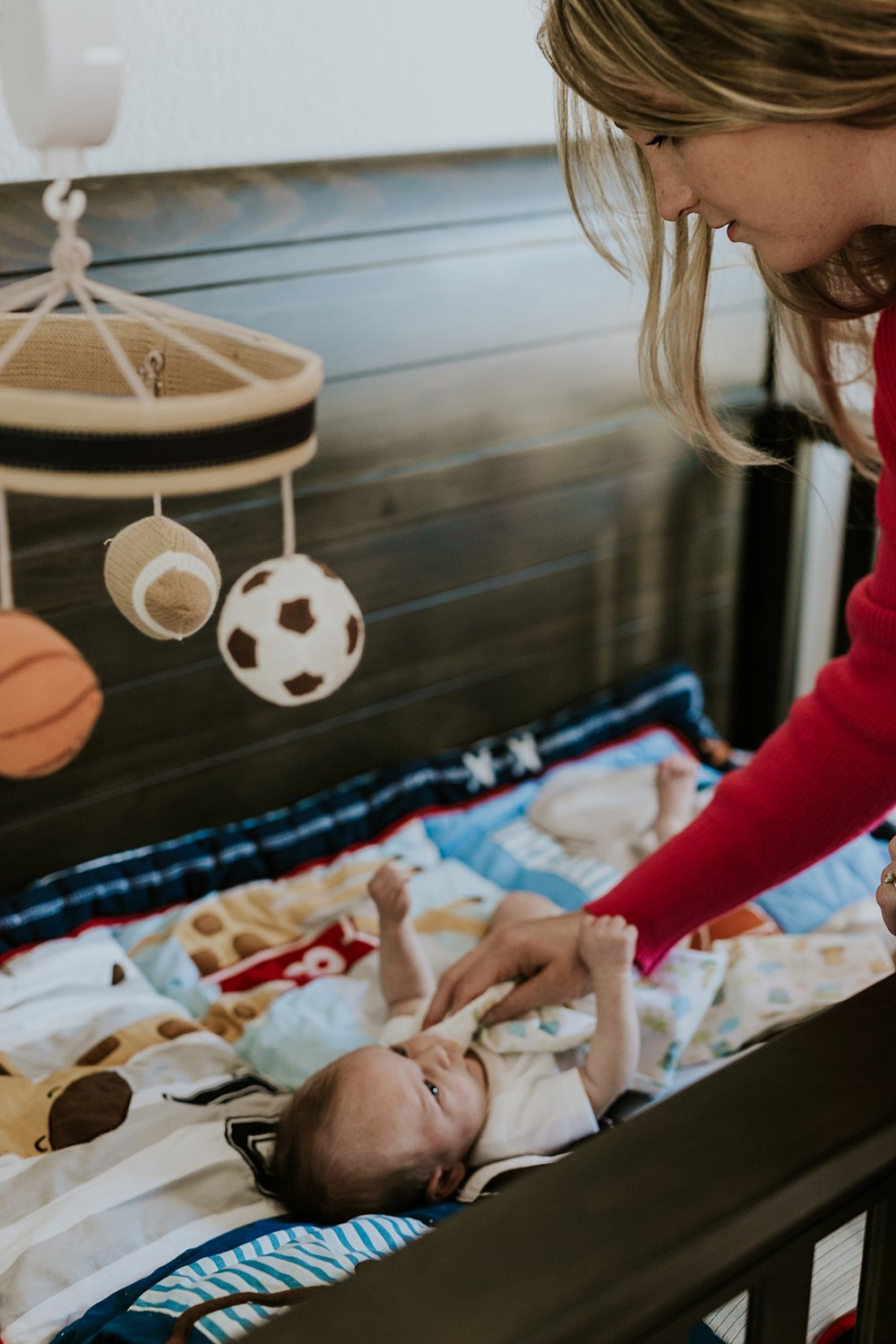 Orange County family photographer. Photo of mom leaning over to touch her newborn son while he lays in his crib during newborn photo shoot in Mission Viejo Orange County