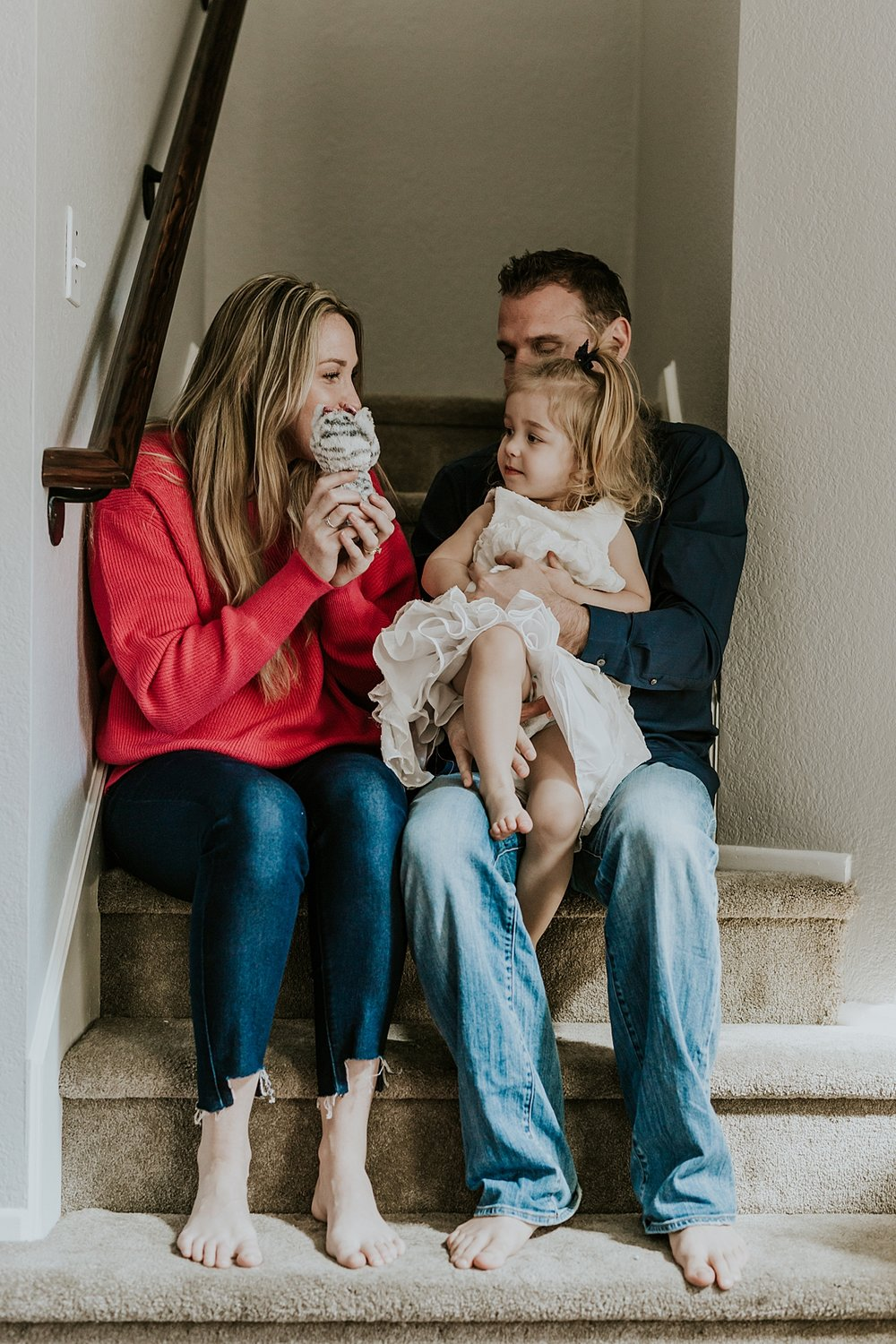 Orange County family photographer. Photo of mom, dad and daughter taken on the stairs of their family home during newborn photo shoot in Mission Viejo Orange County