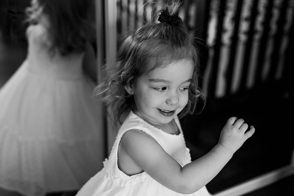 Orange County family photographer. Candid black and white portrait of young girl spinning around in her lovely white dress during newborn photo shoot in Mission Viejo Orange County