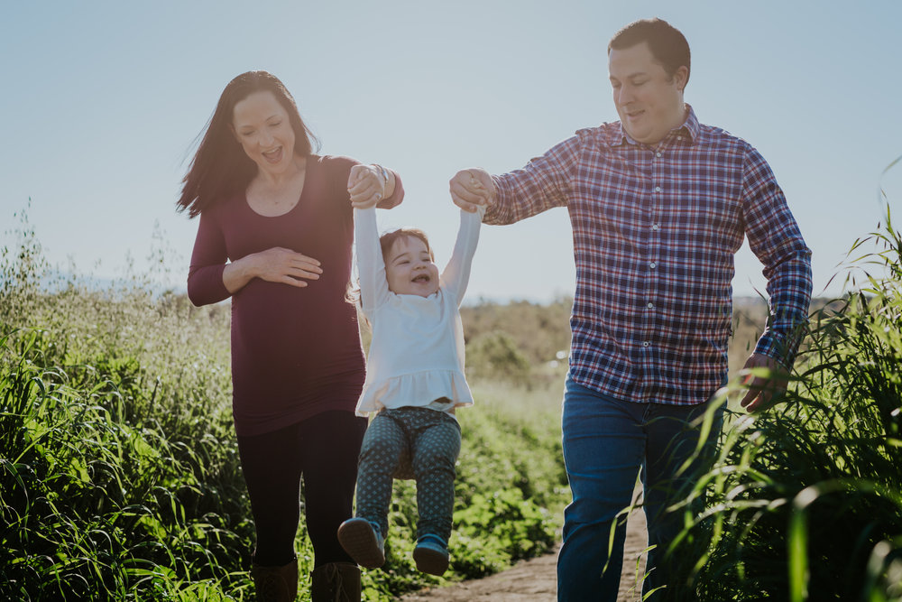 Orange County family photographer. Pregnant mom and dad swing young toddler girl in the air among bright green fields at Quail Hill Irvine
