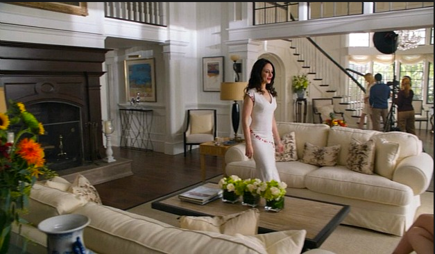 Pop of orange in the floral arrangement on either side of the set, with Victoria wearing a neutral colored dress accented by a pop of color. Green and white flowers set on the coffee table and in back by the staircase.