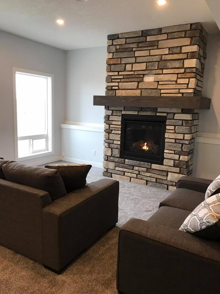 stone fireplace with wood mantel in a new basement development
