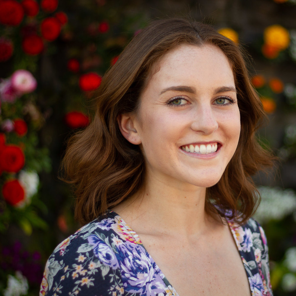 Headshot of Hanna in front of a wall of flowers