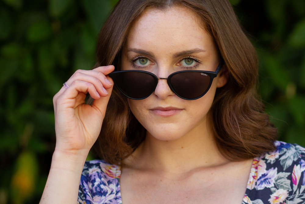 Headshot of Hanna holding sunglasses