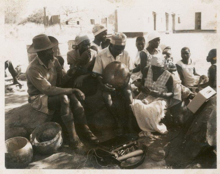 ILAM Photograph collection #ILM00426 381_Johani holds karimba while listening to playback_1969. Seated next to him on the right is Sinati Kadende (known these days as Sinati Nyamande) and seated behind her, also in the white headwrap, is Mavis Bandeira.