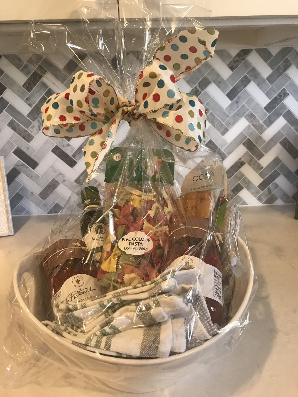 PASTA NIGHT BASKET   Enjoy a delicious pasta dinner with your family! Included in this large ceramic bowl are 3 dish towels, five color pasta, (2) pasta sauces, infused olive oil, and bamboo serving spoons.  DONOR: Laura Bridgeman VALUE: $50