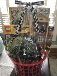TOYS FOR BOYS BASKET   Your boys will go bonkers for this basket full of toys. Included are a Darth Vader mask, LEGO Batman set, StikBots, Avengers and Transformers-themed items, a stunt car, and the super popular Fingerlings T-Rex.  DONOR: Kindergarten Classes VALUE: $95