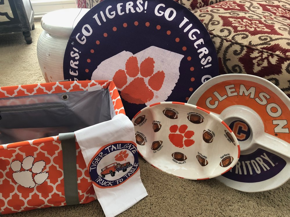 ULTIMATE CLEMSON TAILGATE BASKET   Show your blood runs orange and purple with this ultimate Tiger tailgate collection. Included in this Clemson market tote are Clemson Door Hanger, Clemson ceramic dish, Clemson chip & dip, and Clemson tea towel.  DONOR: 2nd Grade Classes VALUE: $160