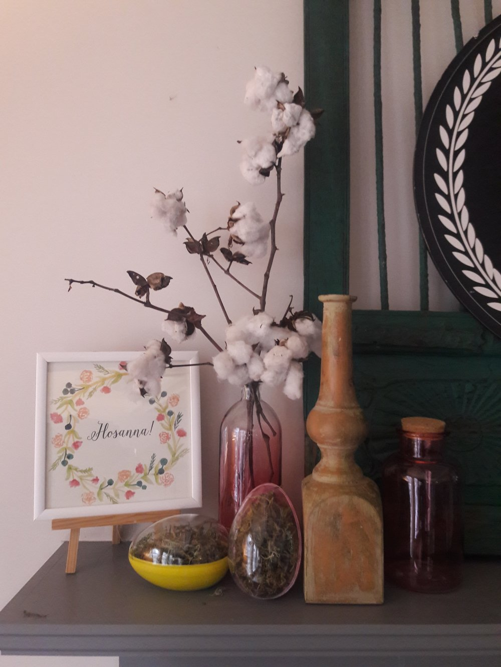 """Hosana"" Printable I found  here , plastic colored eggs from the $1 isle at Michaels, a bag of moss from Dollar store,  pink glass bottles from Target dollar isle ($3 each). The cotton stems I already had, along with the wood candle stick."
