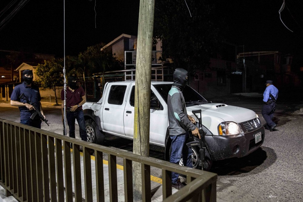 Police armed men, guarding the area where some weapons that are believed to have been used to massacre three women and a guy few hours before in the capital Tegucigalpa, Honduras.