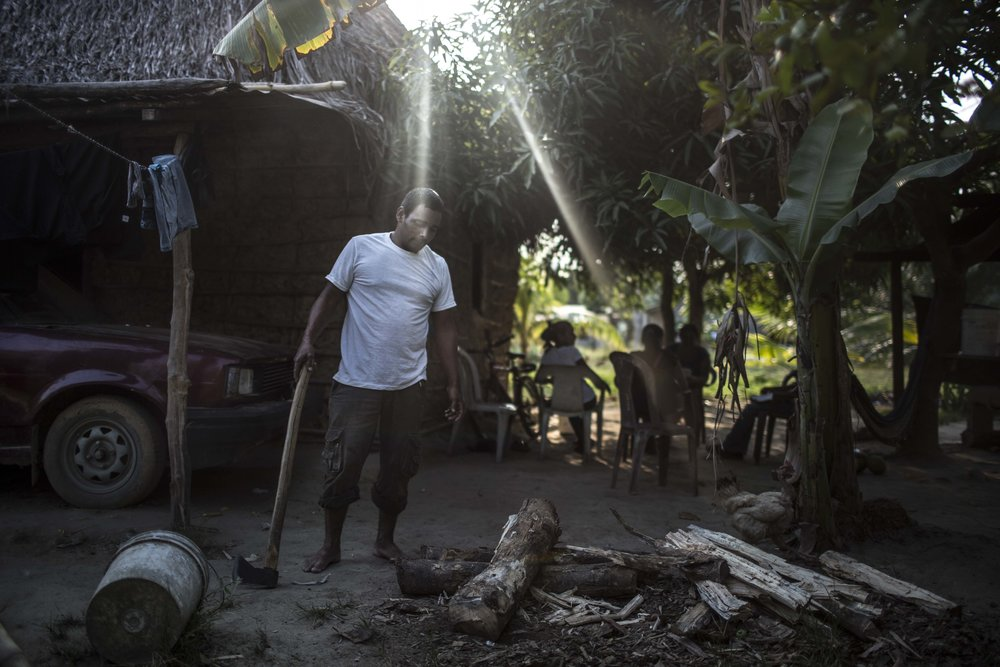 A man in front of his house in the campesino community of Guadalupe Carney in Aguán region, not far from the city of Tocoa in the department of Colon, on the Atlantic coast of Honduras. Community members denounce intimidations by private security forces in the area, in response to the peasants fights for land property and usage. About 60 percent of the palm oil exported from Honduras comes from this region.