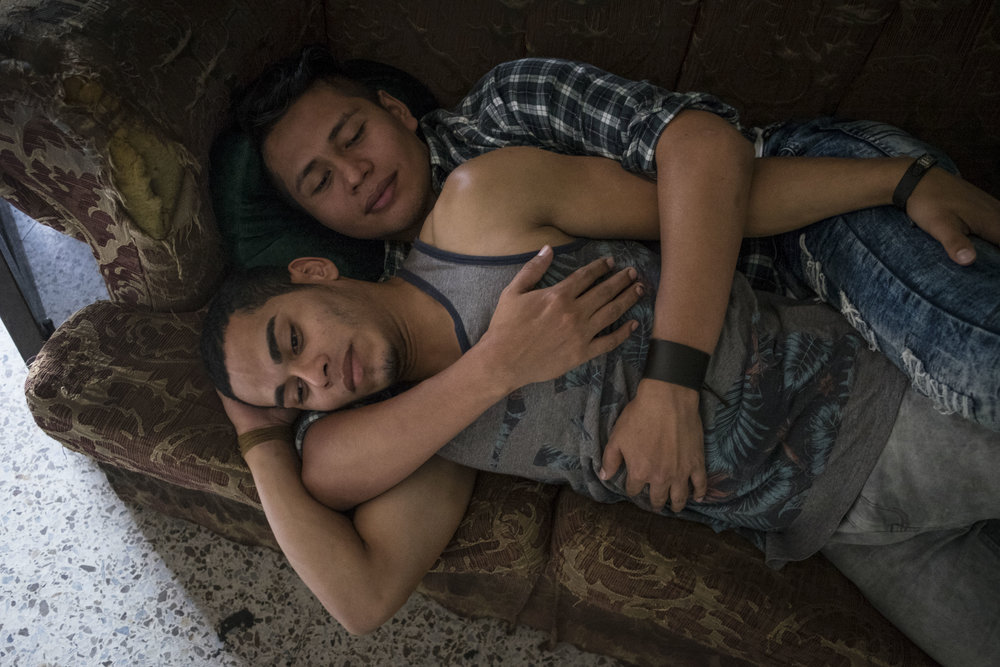 A couple embracing on the sofa in the premises of the LGBT organization Arcoiris, that is a space that aims to reunite homosexuals and transgenders in Tegucigalpa in a place where they can spend time feeling relatively safe.