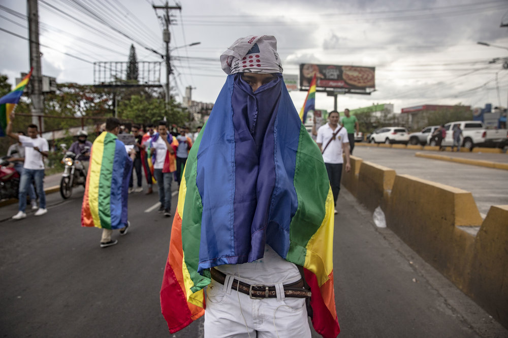 A guy hides his   face while taking part at the Gay Pride parade in May 2016, Tegucigalpa, Honduras. Homosexuality in Honduras is not a crime itself, however, LGBT community members are afraid to be identified and target while out of the crowd.