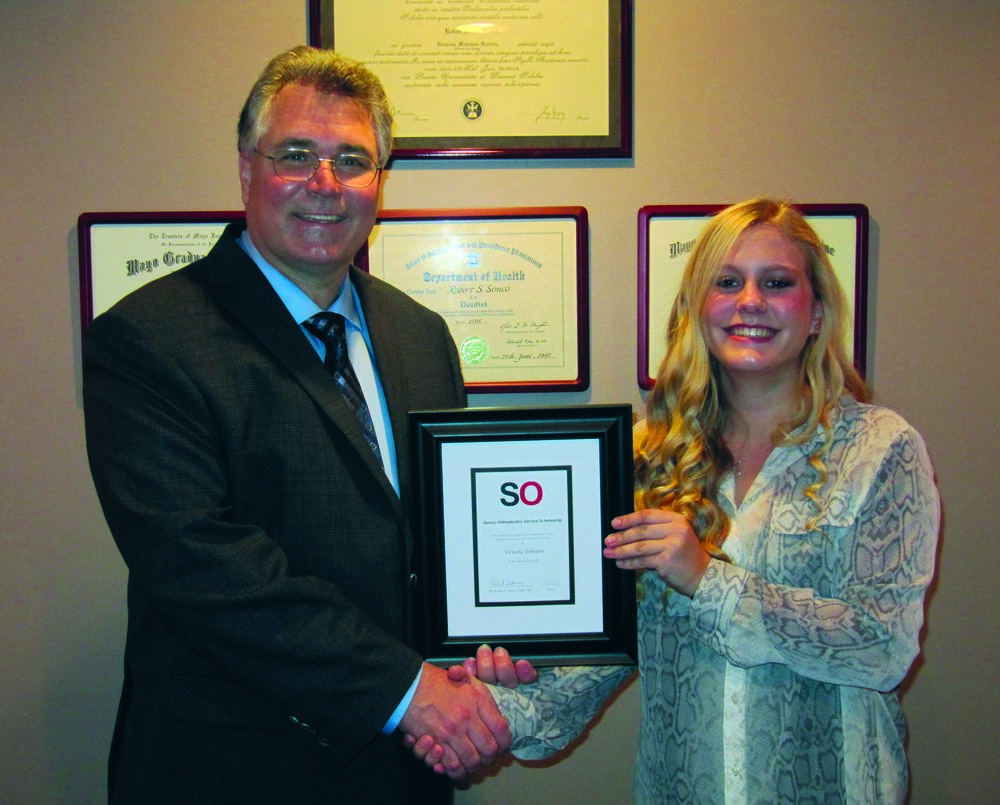 Victoria Johnson receives her Service Scholarship certificate from Dr. Semco!