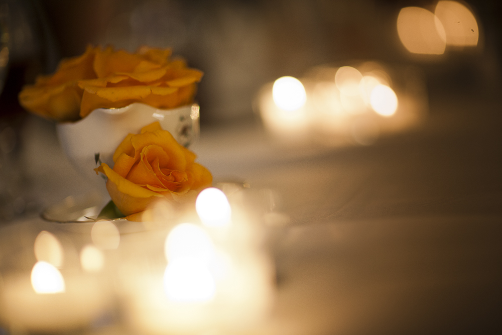 Romantic orange roses and candles adorn the tables at the wedding reception