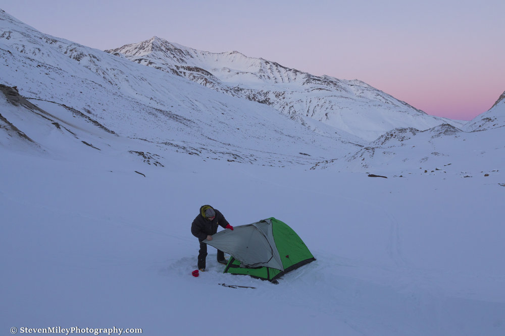 Forrest sets up the tent beside Augustana Glacier shortly after sunset.