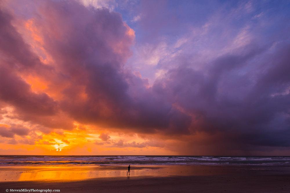 Sunrise illuminates offshore rain clouds over the Atlantic Ocean.Cocoa Beach, Florida.