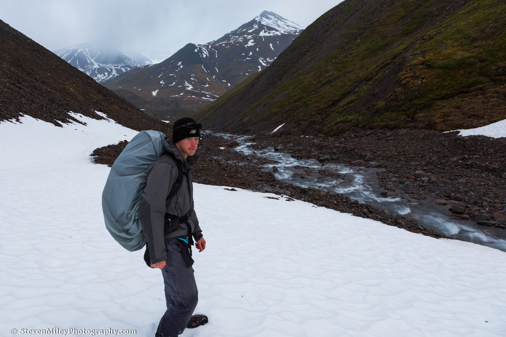 """1:33 A.M. - Hiking down from the pass over lingering snow patches. (That's my """"I love Alaska"""" face.)"""