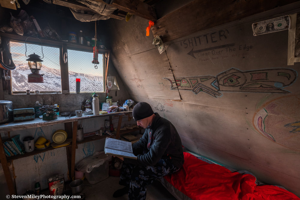 Reading the logbook. The hut is well-stocked with fuel, cooking utensils, and other gear, but some (all) of the food could use tossing.