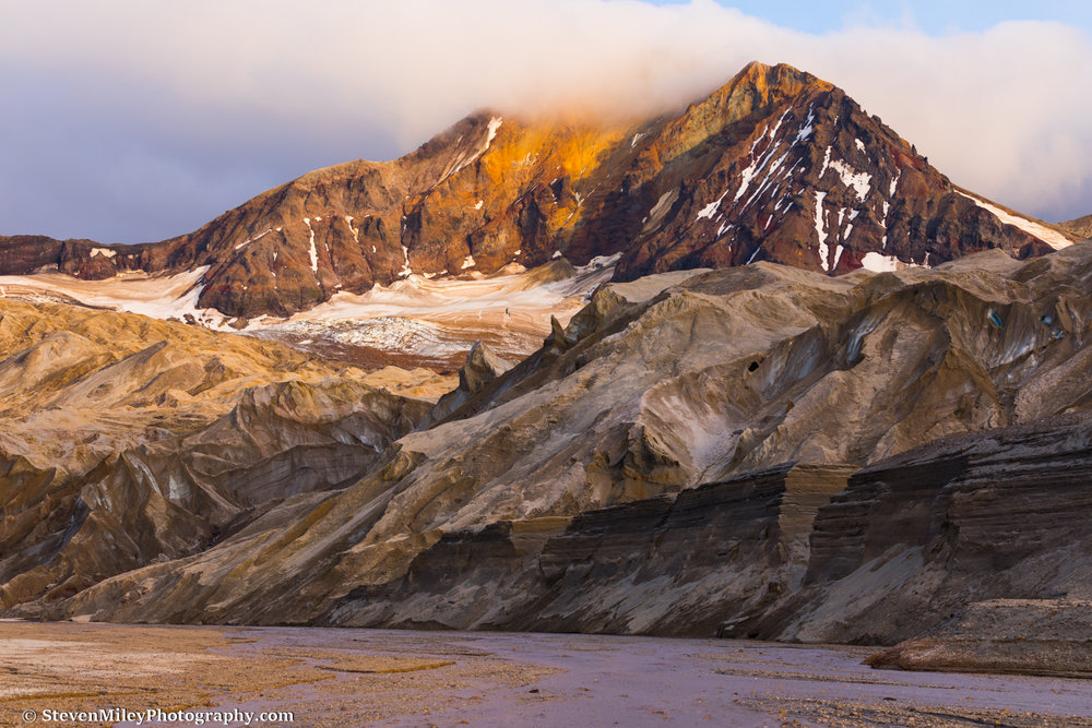 The eastern summit of Trident Volcano rises above one of the Knife Creek Glaciers near sunset.