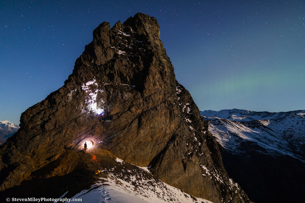 Grant climbing Devils Thumb in the dark with Matt belaying. The rising moon is casting a warm glow on the mountains.