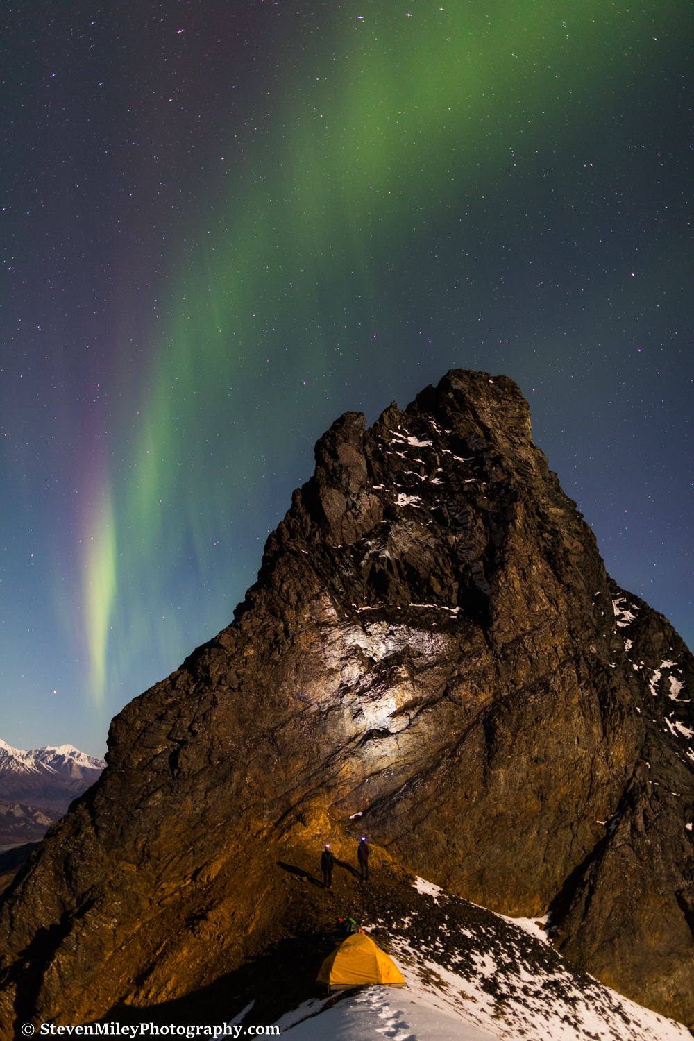 Grant and Matt light up Devils Thumb with their headlamps as the aurora rises.