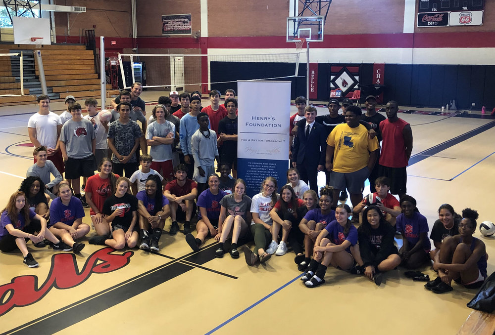 Belle Chasse High School volleyball team and students take a photo with Henry's Foundation President, Elijah Henry.