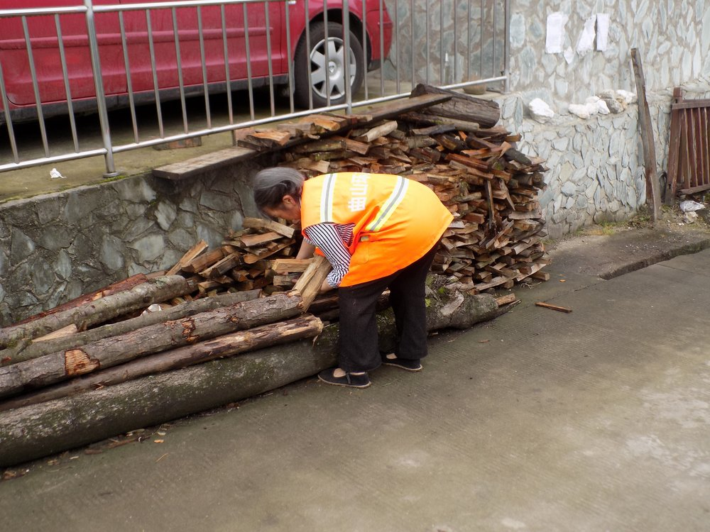 Photo 3: A woman in a small village in Sichuan collects wood (fuel) to burn in her traditional stove. Harvesting and collecting firewood can put an additional burden on households as it requires time that could have been spent doing other things.