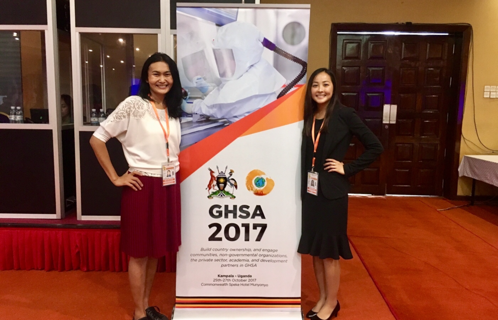 From left to right: Lyazzat Musralina (Institute of General Genetics and Cytology, Kazakhstan) and Ashley Tseng (McGill University, Canada) are shown here standing next to the Global Health Security Agenda 2017 Ministerial Meeting banner in Kampala, Uganda.