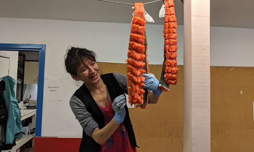 Sheila Veevee prepares arctic char that was donated by a local hunter to the Pangnirtung Soup Kitchen.