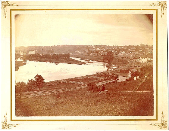 1870s photograph of riverfront, railroad, and mills in distance