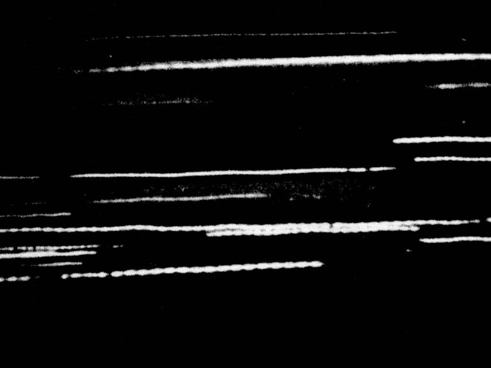 "Night Train     Guy Sherwin   1979 | 2 minutes | UK | 16mm | b&w | sound  The sound of lights passing through a darkened landscape seen from a moving train.  ""Night Train may be seen as continuing the Vertovian tradition of employing film to reveal phenomena not normally visible to the naked eye."" -Nicky Hamlyn"