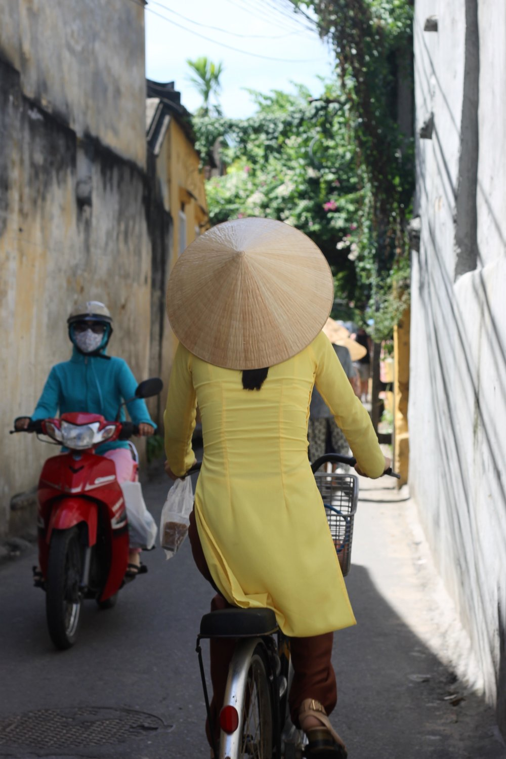 A woman wears a traditional conical hat and Vietnamese áo dài dress in Hoi An.