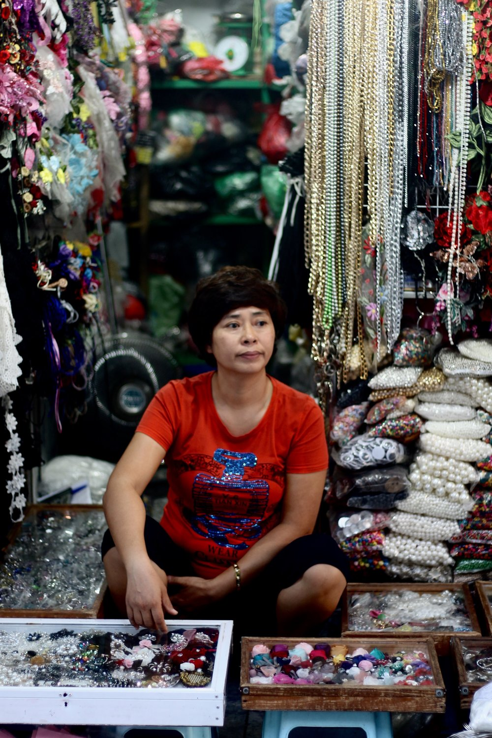 "Woman sits on a tiny plastic stool amidst her shop's goods on ""sewing street"" in Hanoi's old quarter."