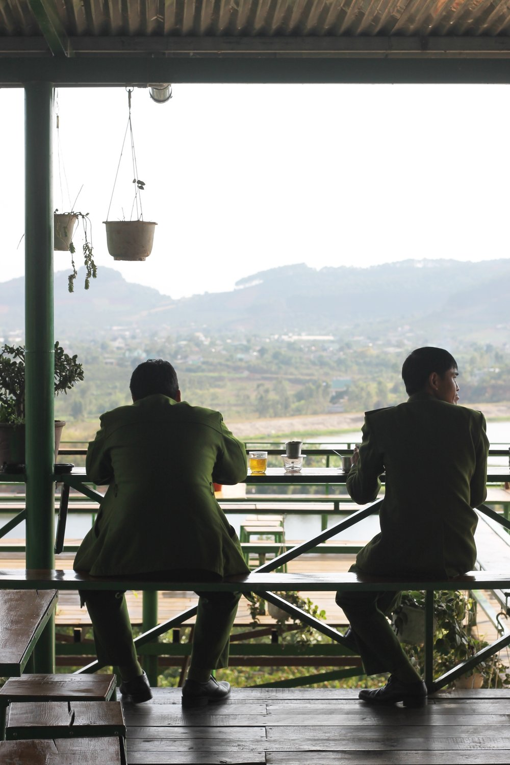 Two traditionally dressed police officers sip coffee at Me Linh coffee farm in the highlands of Da Lat.