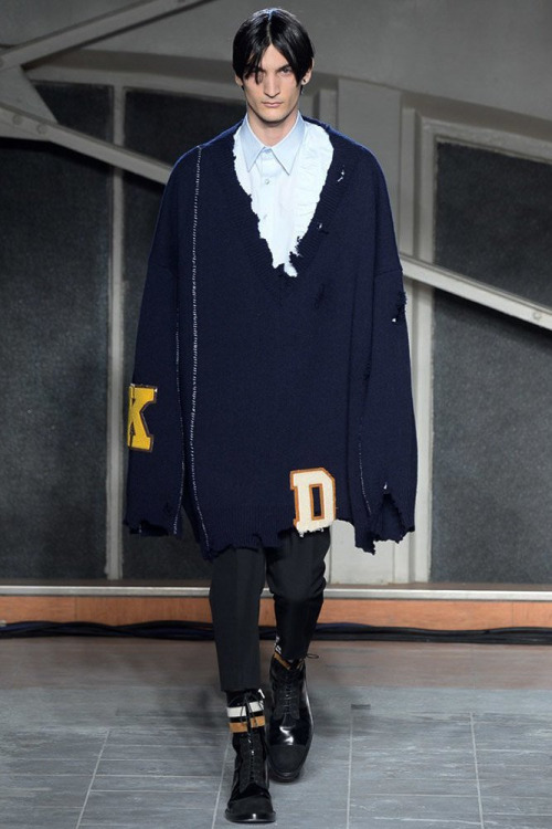 The first look? An overtly oversize distressed sweater with felt lettering placed in seemingly random areas. Photo via Yannis Vlamos.