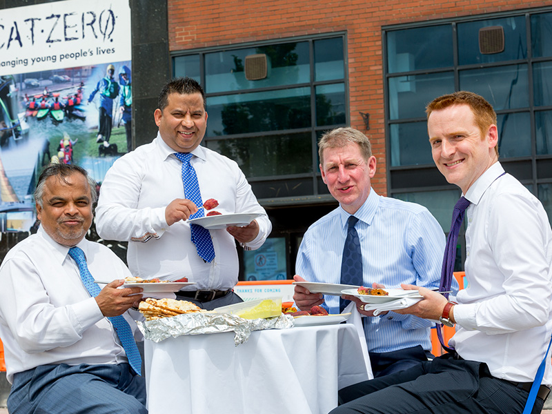 Tapan Mahapatra, left, and Mukesh Tirkoti enjoy an impromptu Tapasya meal with Wykeland Group's Property Director David Donkin and Development Surveyor Tom Watson, right, outside the former CatZero building which is being converted into Tapasya @ Marina.