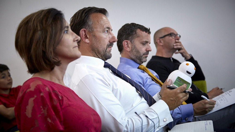 "Richard Beal examines the Robot Reader winning product as fellow ""Dragons"", from left, Diana Taylor, Dominic Gibbons and Jonathan Elvidge hear about the multi-lingual reading device created by children from Hull's Chiltern Primary School."
