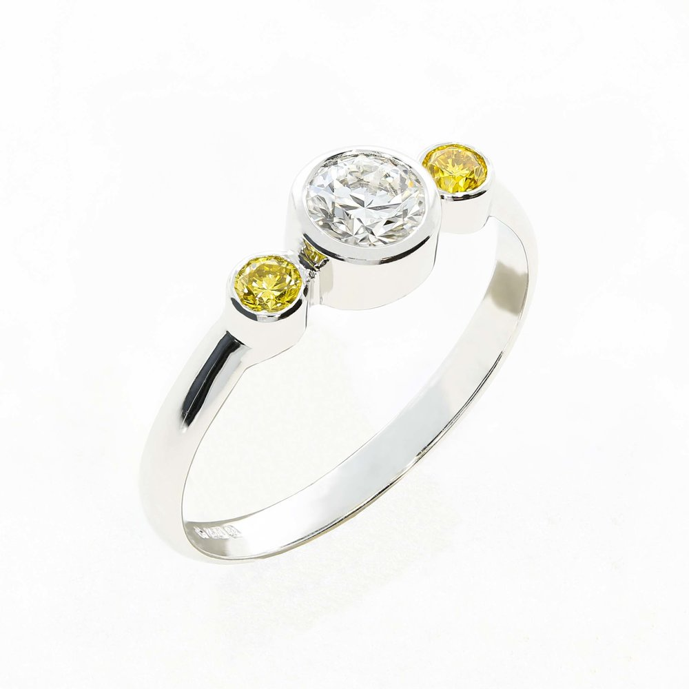 A bespoke Queensmith  trilogy ring  with two intense yellow diamonds and rubover setting