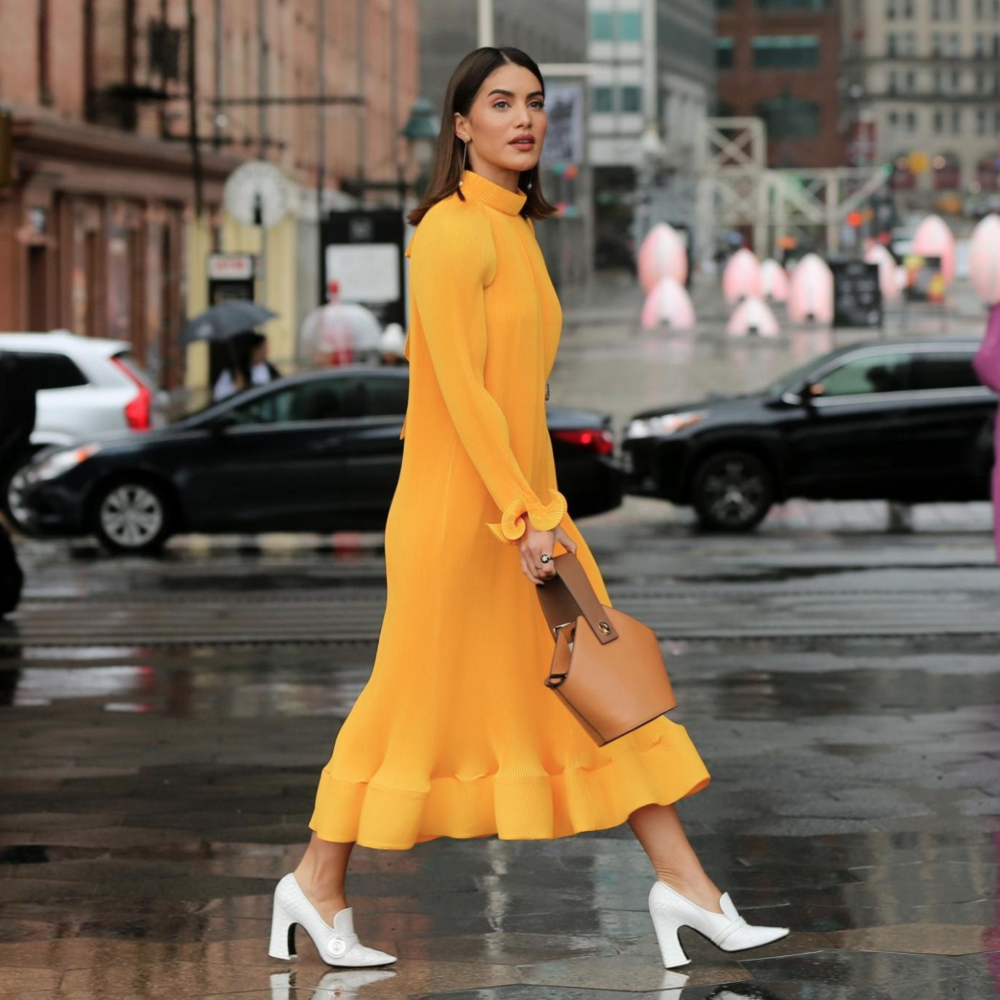 Camila Coelho pairs a tan Danse Lente bag with yolk-yellow dress. Photo by Christopher Peterson/Splash News