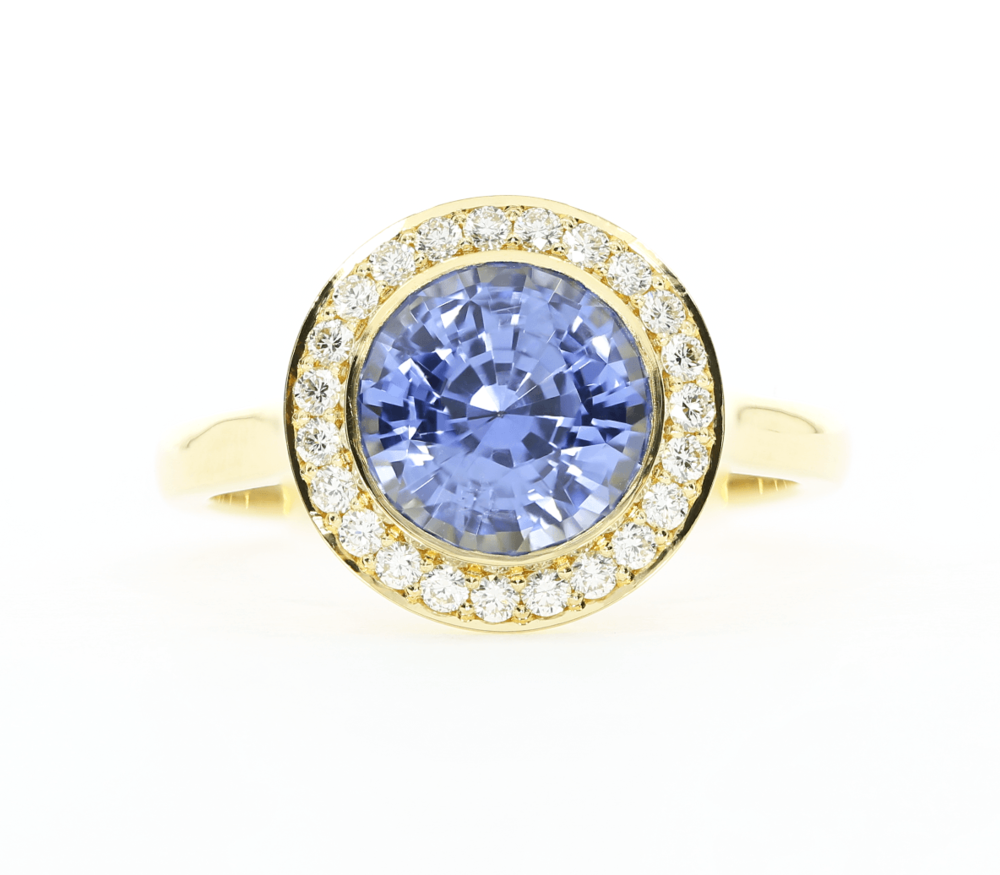Keeping precious stones is the family is a beautiful idea. Round sapphire with a halo of diamonds, set in 18k yellow gold