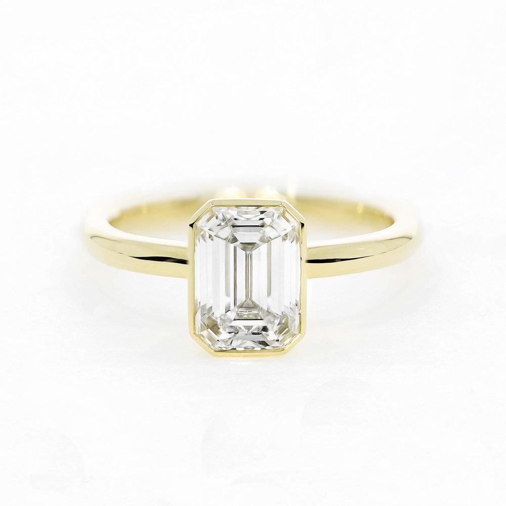A  bespoke design , featuring an emerald cut diamond in rubover setting