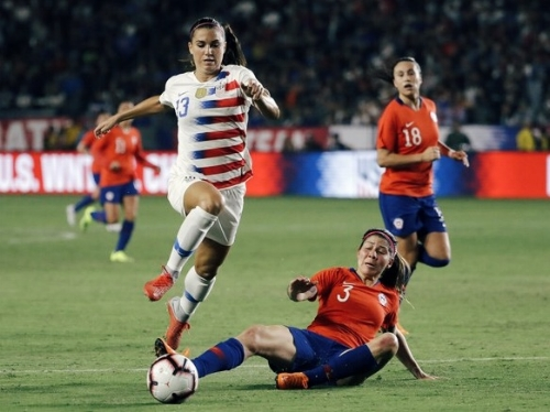United States' Alex Morgan leaps over a slide tackle from Chile's Carla Guerrero in an international friendly. Image: Marcio Jose Sanchez/AP