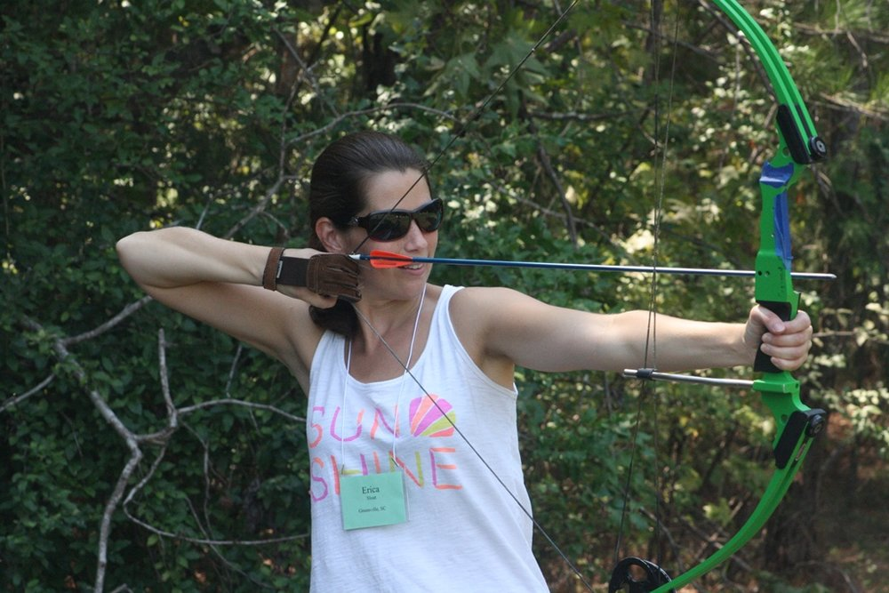 A woman preparing to shoot her bow and arrow.