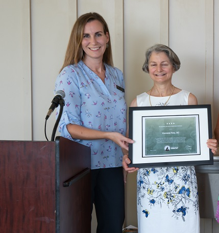 Sara Green, SCWF Director of Education, presents the certificate to Alice Guzick who spearheaded the application for the community.