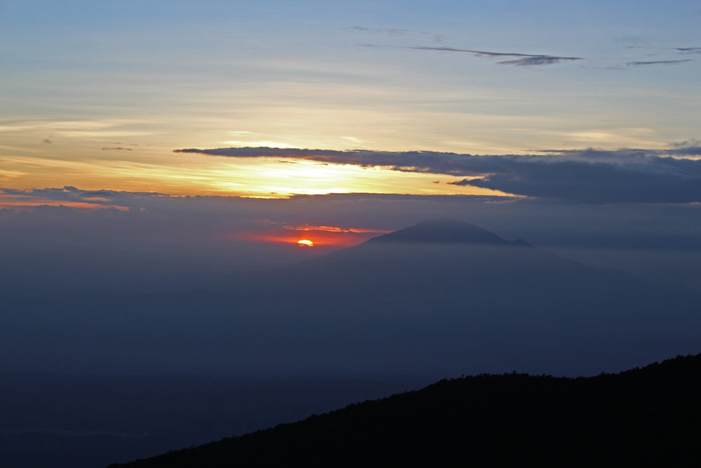 Watching the sun set behind Mount Meru from Karanga Valley Camp on Mount Kilimanjaro