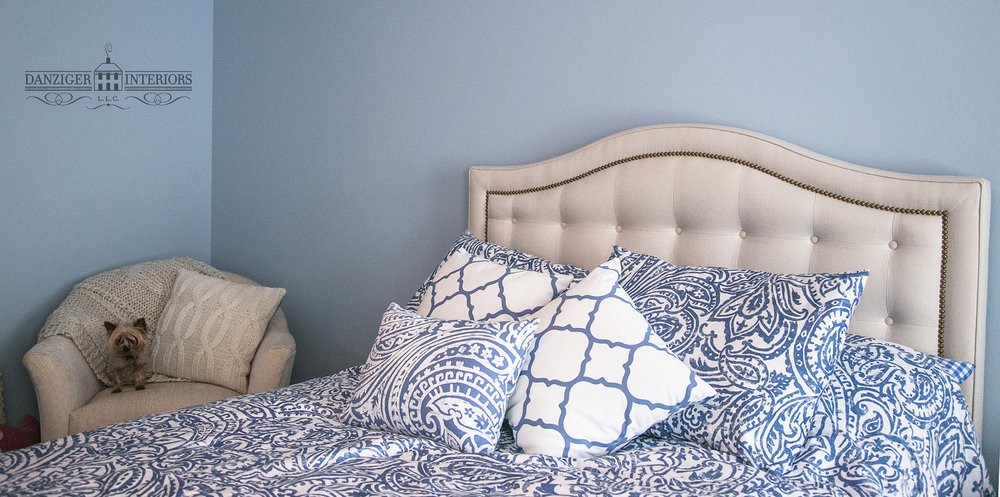 Upholstered headboard and coordinating club chair with new lighter blue walls and linens