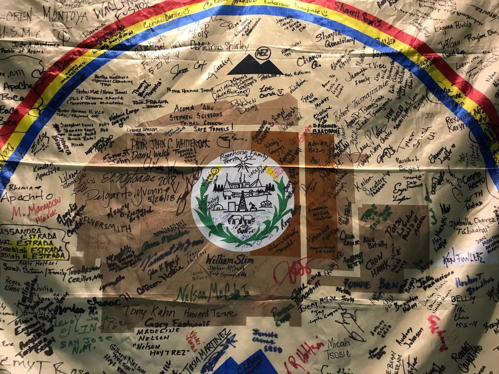 Navajo Nation Flag with the names of Treaty runners, community members, and supporters celebrating the 150 years since the signing of Naaltsoos Sani (Photo taken at Navajo Nation Museum, June 2018).