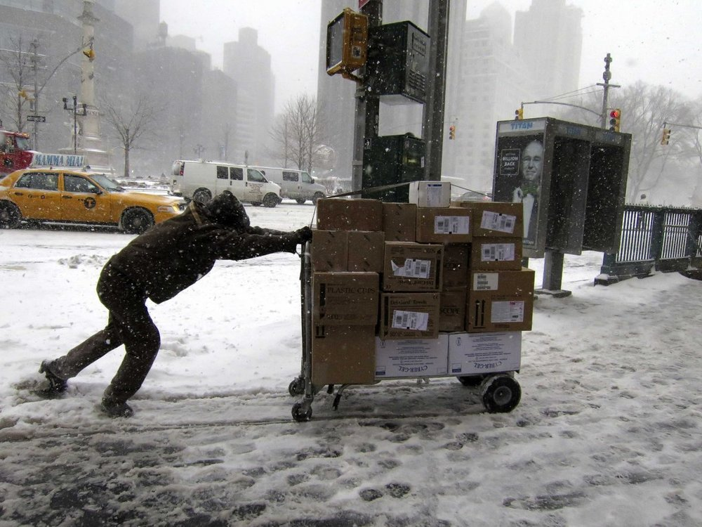 UPS delivery person pushing a cart of packages through the snow. Photo source: Business Insider article of seasonal employees.