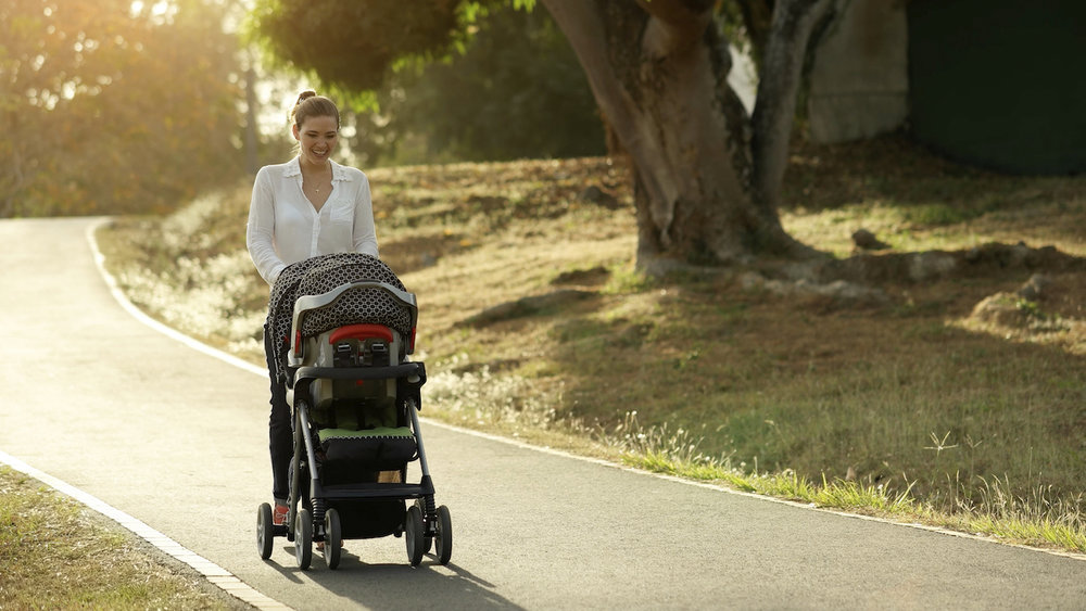 Woman-Mother-Mom-With-Toddler-in-Pushchair-Walking-In-Park-000062076722_Large.jpg
